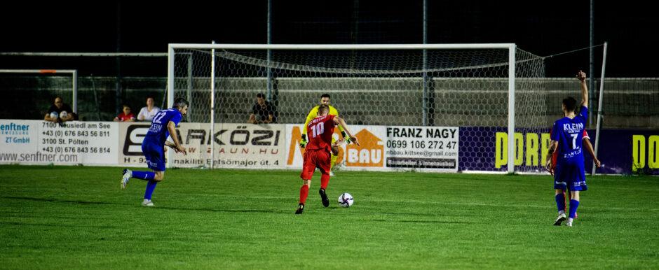 Jozef Sombat splits two Andau defenders